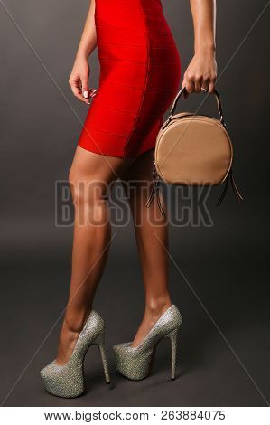 Celebration Evening Fashion Concept. Woman In Red Short Dress Red Spiked Shoes Holding Handbag, Fema