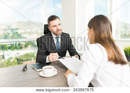 Company Director Explaining Contract Terms To New Employee In Office