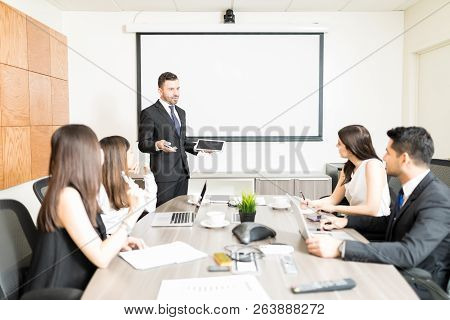 Male Accountant Holding Digital Tablet While Planning Budget With Team In Boardroom