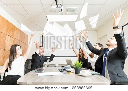 Cheerful Sales Executives Throwing Papers In Midair Over Conference Table