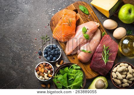 Ketogenic Low Carbs Diet. Meat, Fish, Nuts, Oil, Cheese, Milk And Avocado On Dark Stone Background.