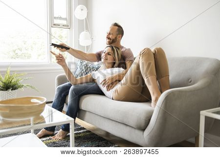 Couple watching tv at home sitting in a comfortable couch in the livingroom at home poster