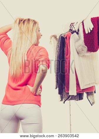 Woman Standing In Wardrobe With Winter Clothes, Can Not Decide What To Wear. Picking Winter Clothing