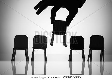 Businessperson Picking Up Chair Amongst Other In A Row