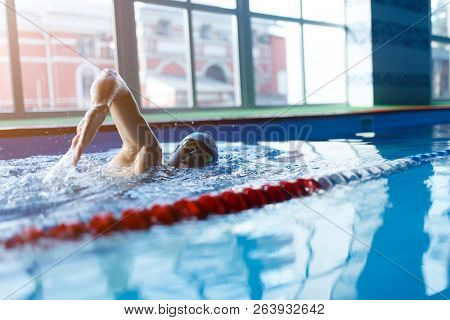 Image of man swimming in pool indoors