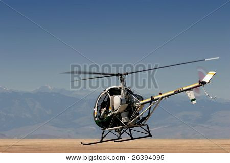 a police / sheriff helicopter flying low over a field