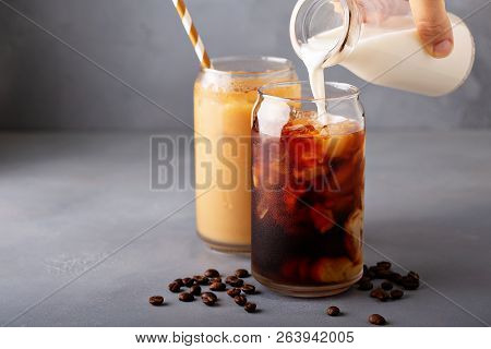 Cold Brew Iced Coffee In A Glass With Milk Or Creamer Pouring Over