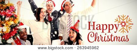 Nice business team punching the air to celebrate christmas  against christmas card