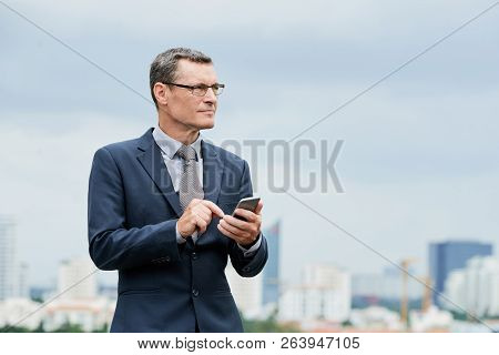 Portrait Of Smiling Ambitious Mature Entrepreneur Dialing Phone Number