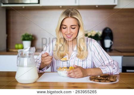 Healthy Breakfast Concept - Young Beautiful Woman Eating Corn Flakes With Milk In Modern Kitchen