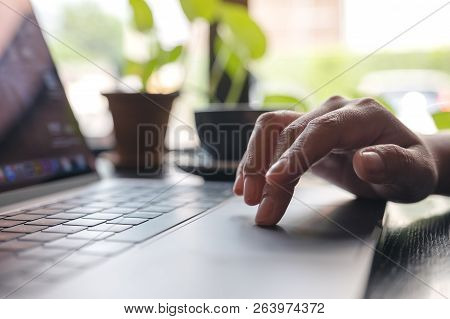 Closeup Image Of Hand Using And Touching On Laptop Touchpad On Table