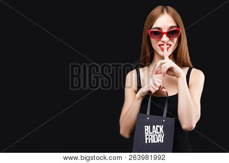 Attractive Long-hair Brunette Woman Wearing Black Dress Holding Black Friday Shopping Bag And Showin
