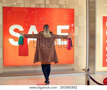 Consumerism, Shopping, Lifestyle Concept Woman In Shopping. Happy Woman With Shopping Bags Enjoying