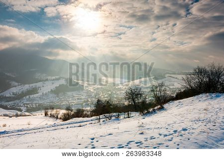 Magical Winter Countryside. Sun Ray Through The Cloudy Sky. Snowy Hill And Leafless Trees. Village D