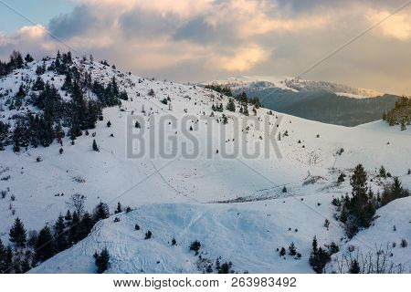 Mountainous Winter Scenery At Dawn. Forested Hills And Distant Alpine Meadow In Snow Under The Cloud