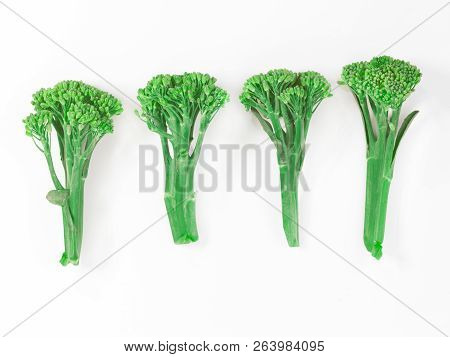 Four Stems Of Green Sprouting Broccoli In A Row