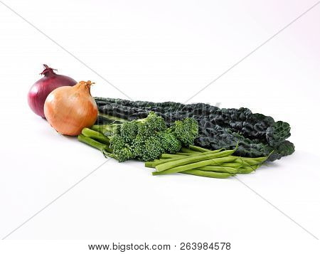 A Selection Of Onions, French Beans Broccoli And Onions On A White Background