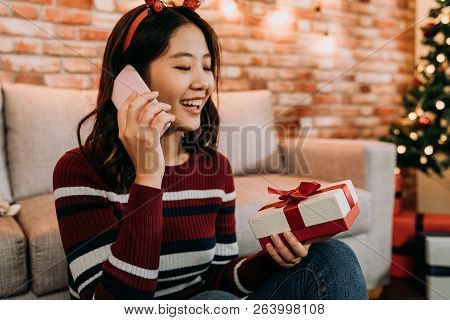 Young Girl Received Gift From Online Christmas Sale. Lady Holding Cellphone And Gift Box Talking On