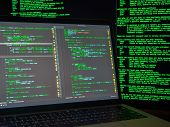 Breaching system using two monitors. Green php coding lines on the dark background. Hacking concept poster