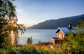 Norwegian wooden summer house (Hytte) with terrace overlooking scenic lake at sunset, Telemark, Norway, Scandinavia poster