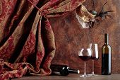 Red wine on a old wooden table. Old masquerade Venetian carnival mask with feathers and rhinestones on a background of brown wall. Copy space. poster