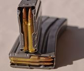 Two metal rifle magazines, one stacked upon the other, loaded with .223 caliber bullets poster