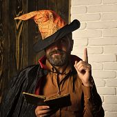 Halloween mystic story, manuscript, fairytale. Wizard reading book on wooden and brick wall. Magic and evil spell. Philosophy, wisdom, knowledge concept. Man in witch hat and cloak with raised finger. poster