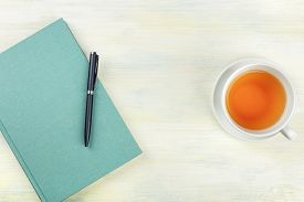 A Photo Of A Teal Blue Journal With A Pen And A Cup Of Tea, Shot From Above, Forming A Frame On A Li
