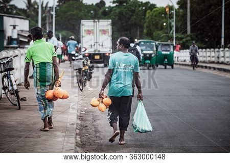 Negombo, Sri Lanka. July 20, 2016: Some People Walking With Recent Purchase At The Fish Market In Ne