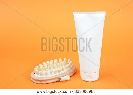 White Blank Cosmetic Tube Of Cream Or Body Lotion And Wooden Anti-cellulite Massager On Orange Backg
