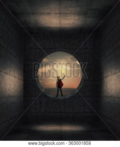 Traveler Looking Through Round Concrete Window To The Sky . Isolated In Dark Concrete Room . Escape