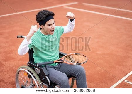 A portrait of teenage boy in wheelchair playing tennis