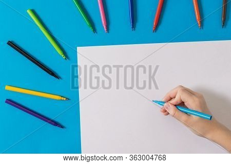 A Hand With A Blue Marker And A White Sheet Of Paper And A Set Of Colored Markers. Universal Markers