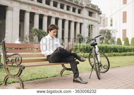 Young Handsome Businessman With Laptop And Bicycle Sitting On Bench In Park