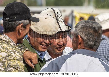 Osh, Kyrgyzstan - June 30, 2019: Four Men, Some With Hat,  An Ak-kalpak, On The Livestock Market In