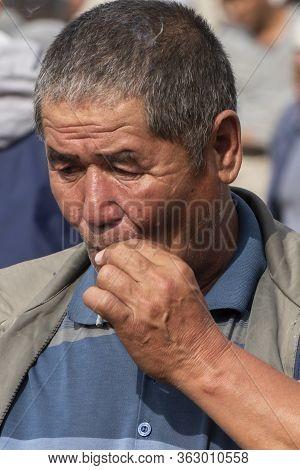 Osh, Kyrgyzstan - June 30, 2019: Smoking Man On The Livestock Market In Osh, Kyrgyzstan.