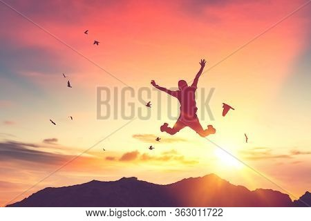 Silhouette Man Jump And Birds Fly On Sunset Sky And Cloud Texture Abstract Background. Copy Space Of