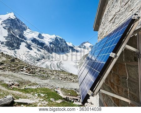 Close Up Of Blue Solar Panels On Wall Of Brick House In Snowy Mountains. Special Equipment Generatin