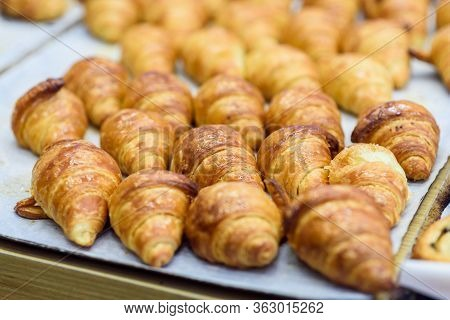 Freshly Baked Croissants On Baking Paper In A Bakery Shop. Warm Fresh Buttery Croissants.