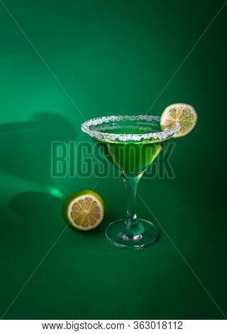 Martini Glass With Green Smoothie And Lime Slice. The Edge Of The Glass Is In Sugar. Lime Is Next To