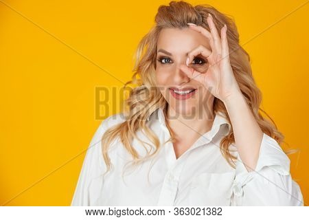 Blond Woman Feeling Optimistic Happy Showing Ok Circle Over Eye Smiling Happily. Feels Happy Optimis