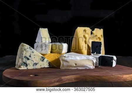 Different Types Of Cheeses. Slices Of Brie Cheese Or Camembert With Parmesan, Cheddar, Blue Cheese,