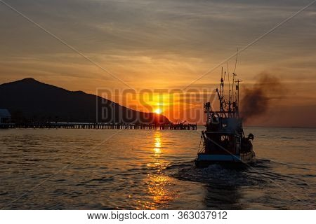 The Fishermen Drove The Fishing Boat To The Sea On Sunset And Dramatic Clound.silhouette Of Fishing