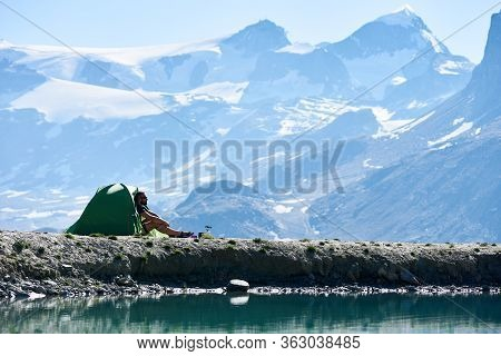 Side View Of Male Traveler Sitting Inside Tourist Tent With Majestic Rocky Hills On Background. Man