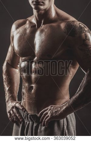 Studio Portrait Of A Shirtless Athletic Tattooed Male.