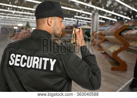 Security Guard Using Portable Radio Transmitter In Shopping Mall