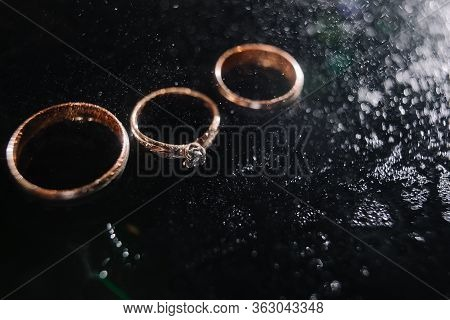 Wedding Rings In Spray Of Water. Golden Rings In A Dark Key. Engagement Ring. Selection Of Rings For