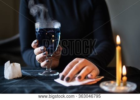Female Hands Holding Magic Love Potion And Occultic Fortune-telling Cards On Dark Background.