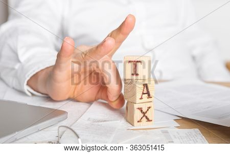Businessman Removes Wooden Blocks With The Word Tax. Reduction Or Restructuring Of Debt. Bankruptcy