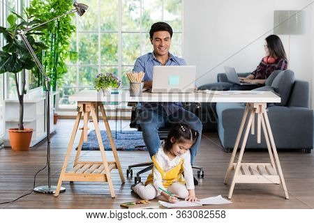 Mixed Race Family Sharing Time In Living Room. Caucasian Father Using Notebook Computer To Work And